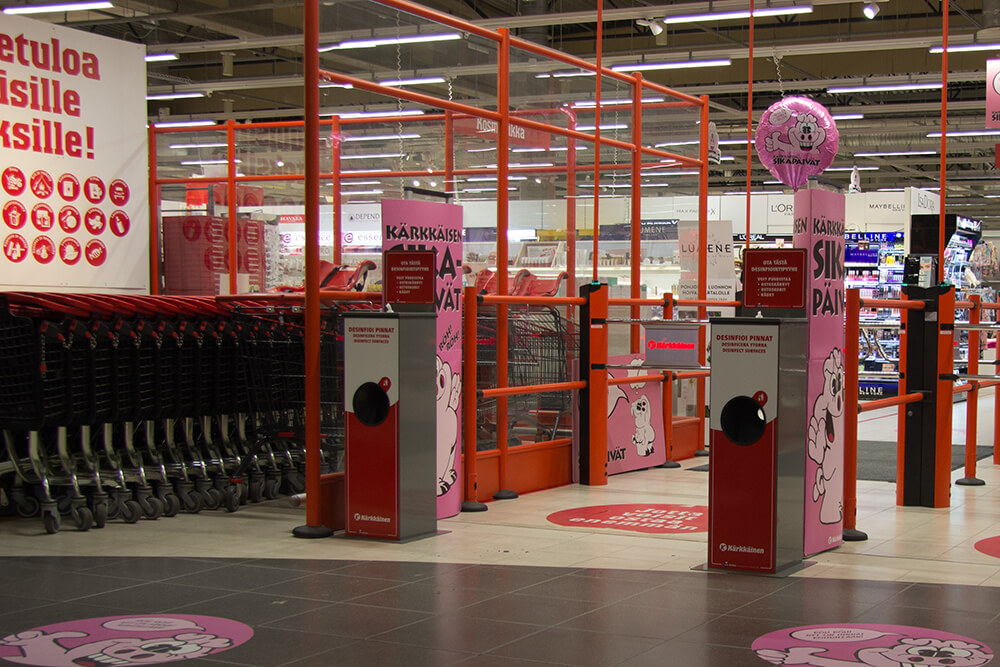 Tavarataloketju Kärkkäisen sisäänkäynti sekä Winwipesin desinfiointipyyhetelineitä.